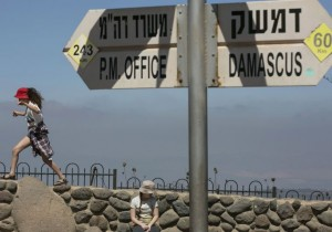 Girls play near a sign at Mount Bental, an observation post on the Israeli side of the Golan Heights, overlooking the Syrian side of the Kuneitra crossing. (photo credit:REUTERS/BAZ RATNER)